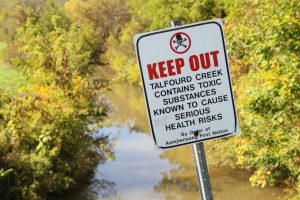 A sign warns the public of toxic pollution in the water due to the chemical plants.